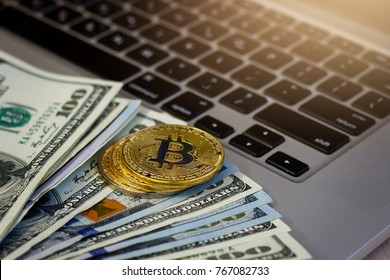 Bitcoin golden coins on a dollar banknotes office background  white laptop mobile