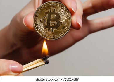 Bitcoin in hand on white background match, fire, flame, burning