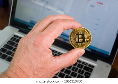 Bitcoin held in front of a laptop with price trend graffic