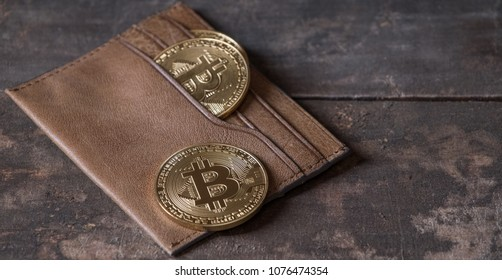 Bitcoin in leather wallet on wooden table top
