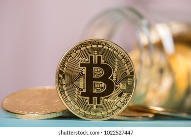 Bitcoin in mason jar against pastel background colors.