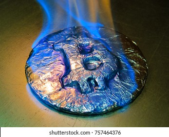 Bitcoin metal silver coin is burning with blue flame. It means hot price or value and high exchange rate of crypto currency on market. It is crisis and fall to lose investments due to financial risk