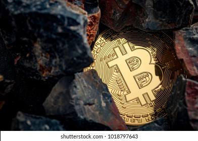 Bitcoin mining and cryptocurrency concept with a golden coin submerged in black stones compared to the traditional gold mining
