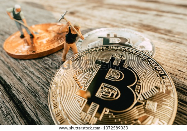 Bitcoin Mining miniature people diging on valuable coin wood background
