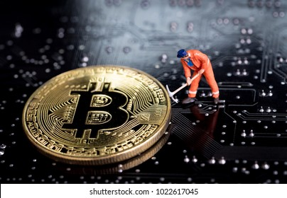 Bitcoin mining miniature worker, small figure holding mattock digging on shiny golden Bitcoin crypto currency coin on electronics cyber look circuit board with soldering.