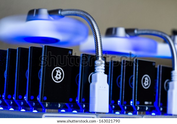 Bitcoin mining USB devices in a row with small fans.