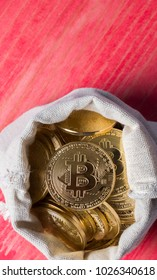 Bitcoin in money pouch on red wooden table top