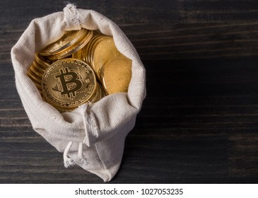 Bitcoin in money pouch on wooden table top
