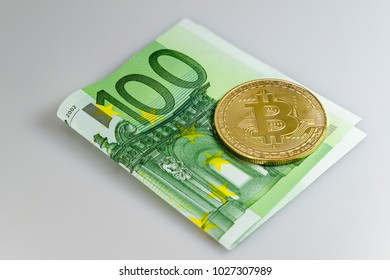 A bitcoin on a 100 euro bill in front of a white background