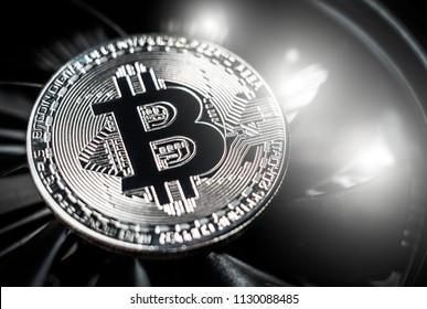 Bitcoin on cooling computer fan background. Silver bitcoin coin on spinning blades of ventilator