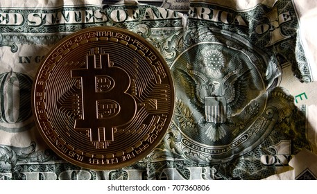 Bitcoin on Crushed dollar banknote against the seal of USA.Concept of  Monetary system collapse .