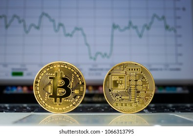 Bitcoin on a laptop with price trend graffic on the background