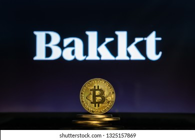 Bitcoin on a stack of coins with Bakkt logo on a laptop screen. Cryptocurrency and blockchain adoption getting mainstream. Slovenia - 02 24 2019