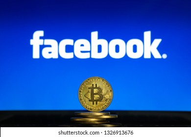 Bitcoin on a stack of coins with Facebook logo on a laptop screen. Cryptocurrency and blockchain adoption getting mainstream. Slovenia - 02 24 2019