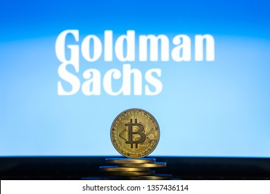 Bitcoin on a stack of coins with Goldman Sachs logo on a screen. Cryptocurrency and blockchain adoption getting mainstream. Slovenia - 02 24 2019
