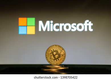 Bitcoin on a stack of coins with Microsoft logo on a laptop screen. SLOVENIA, LJUBLJANA - 02.24.2019