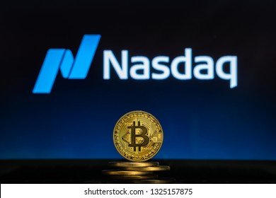 Bitcoin on a stack of coins with Nasdaq logo on a laptop screen. Cryptocurrency and blockchain adoption getting mainstream. Slovenia - 02 24 2019