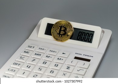 A bitcoin on a white calculator in front of a white background
