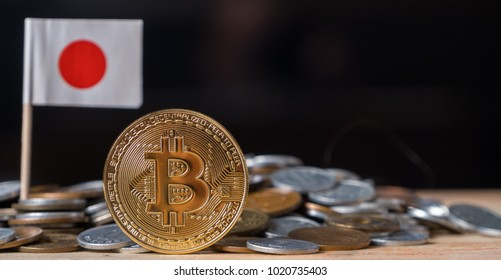 Bitcoin on wooden table with mini Japanese coins and flag