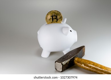 A bitcoin in a piggy bank and an old hammer in front of a white background
