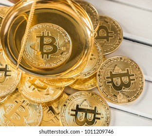Bitcoin replica with weight scale over white wooden tabletop background
