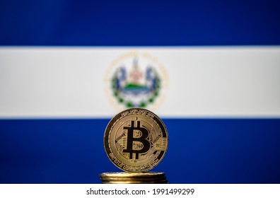 Bitcoin representation coin placed in front of blurred Salvador's national flag. El Salvador is the first country to adopt bitcoin as legal tender. Concept. - Shutterstock ID 1991499299