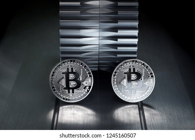 Bitcoin Silver coin stand on metallic surface with gearwheel in the background