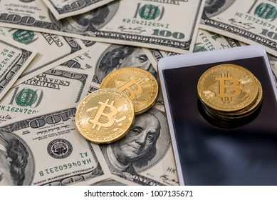 Bitcoin, smartphone on dollar bills