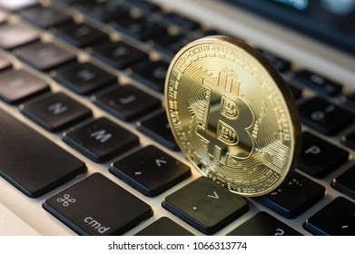 Bitcoin standing between the keys of a keyboard of a laptop