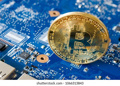 Bitcoin standing on the electronic motherboard of a laptop