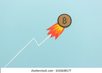Bitcoin surging to record high  - conceptual image of a bitcoin coin with fire rising up