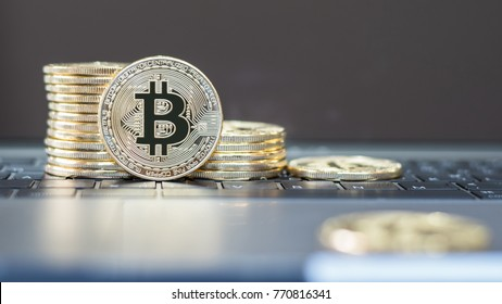 Bitcoin symbol among piles of golden coins for Blockchain transfers via internet digital crypto currency on computer fintech banking technology and initial token offering (ITO) concept