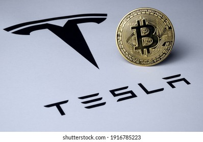 Bitcoin and Tesla logo seen on paper document. Concept for investment in cryptocurrency. Selective focus. Stafford, United Kingdom - February 14, 2021.