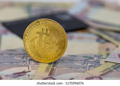 Bitcoin token on top of Dubai, dirham banknotes money with black credit card. Cryptocurrency versus paper currency versus credit card concept