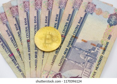 Bitcoin token on top of Dubai, dirham banknotes money. Cryptocurrency versus paper currency concept, flat lay view