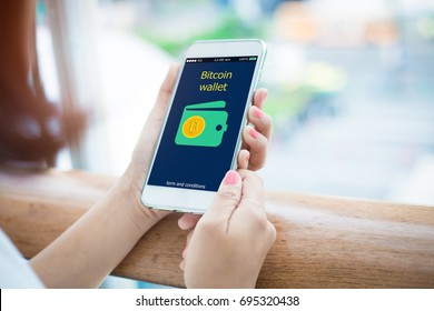Bitcoin wallet.close-up of female hands holding mobile phone