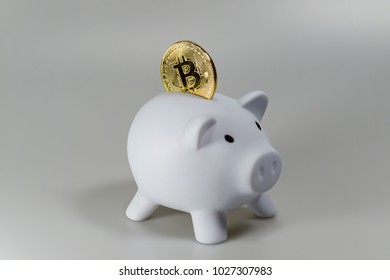 A bitcoin in a white piggy bank in front of a white background