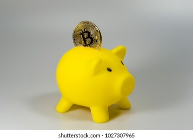 A bitcoin in a yellow piggy bank in front of a white background