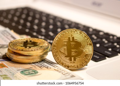 Bitcoins and 100 dollar bills on a black and white laptop keyboard. Concepts of finance, cryptocurrency, markets, and the economy