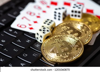 Bitcoins, cards and dices on keyboard. Cryptocurrencie gambling concept
