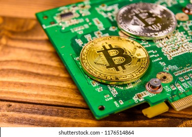 Bitcoins and circuit board on rustic wooden table