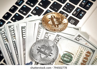 Bitcoins with dollar bills on laptop keyboard.
