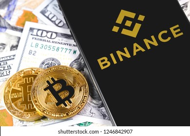 bitcoins, dollars with Binance logo on the screen smartphone. Binance - one of the largest cryptocurrency exchange on the market. Moscow, Russia - December 1, 2018