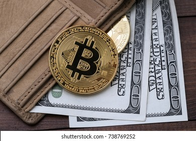 Bitcoins, hundred dollar bills and leather wallet.