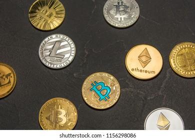 bitcoins, litecoin and ethereum lie on old dark background
