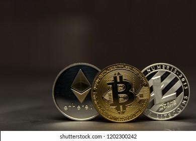 bitcoins, litecoin and ethereum stand on dark backround