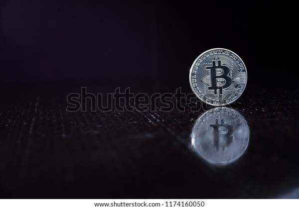Bitcoins and New Virtual money concept. A silver bitcoin on a black table. Copy space.