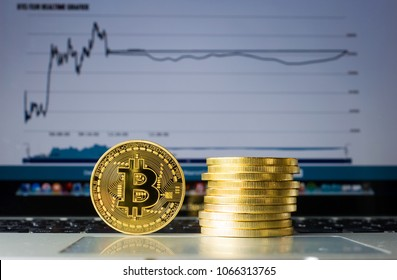 Bitcoins on a laptop with price trend graffic on the background