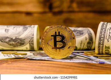 Bitcoins and one hundred dollar bills on rustic wooden table