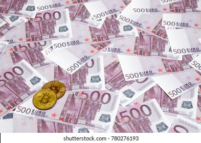 Bitcoins over pile of five hundred euro banknotes. Traditional money versus cryptocurrency concept. Gold coin above 500 euro bills. Close up